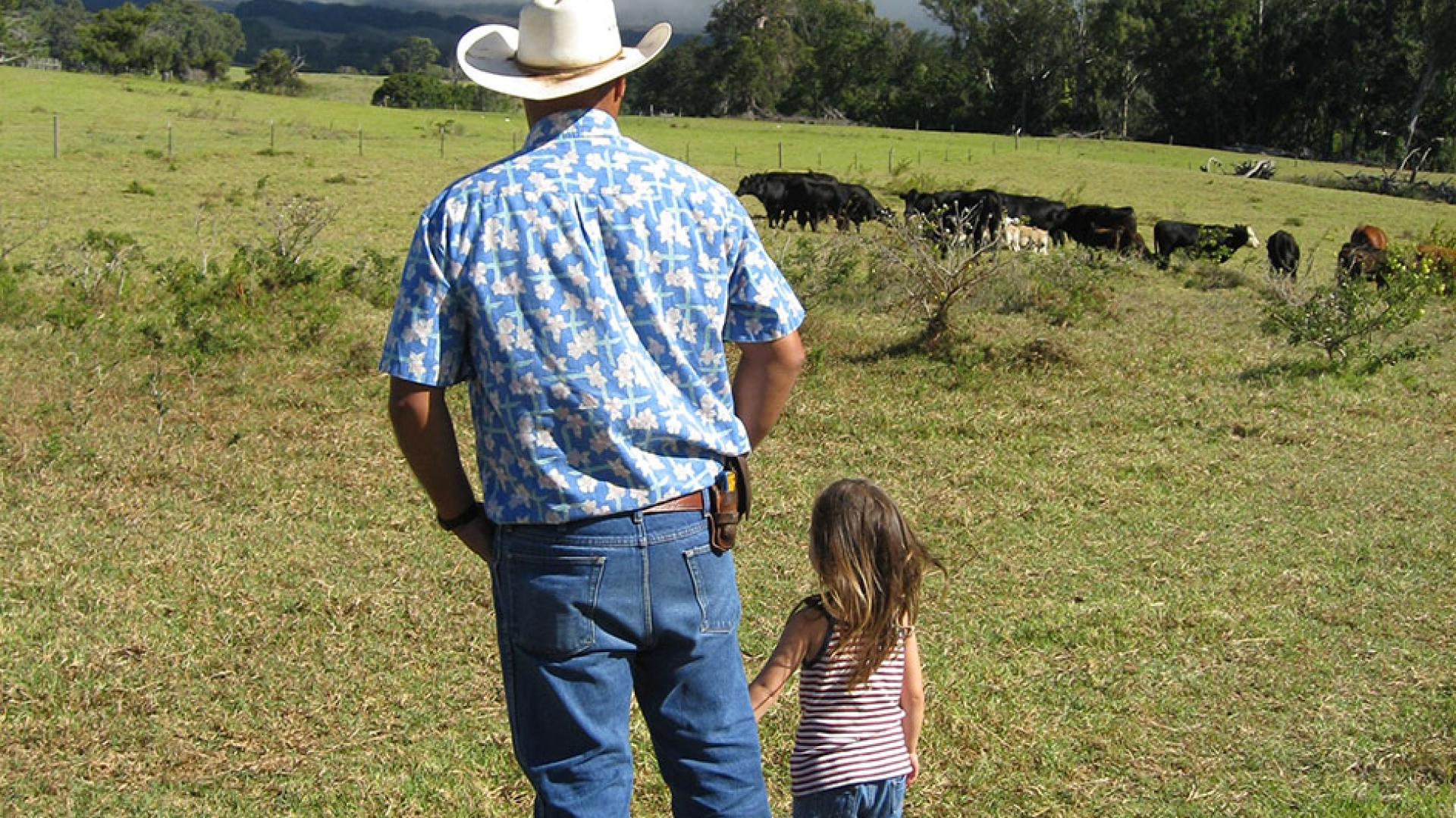 Rancher and daughter looking at cattle